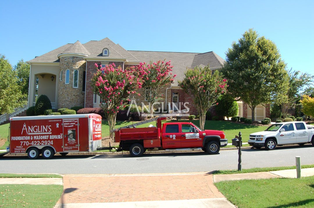 anglins truck with a trailer in front of a building being repaired