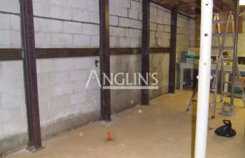 steel support beams in a basement of a bulding and with cracks between the bricks filled