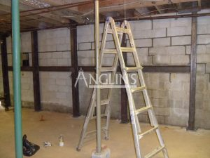 steel support beams in a basement of a bulding and with cracks between the bricks filled, there is a ladder in the foreground