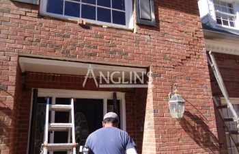 anglin employee repairing cracks in a wall of a house