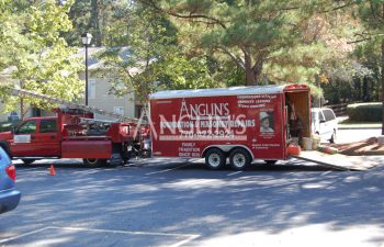 anglin truck and trailer parked next to a house that needs repair