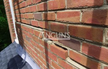 wall of a house with cracks between the bricks