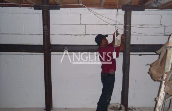 anglin emplooye working on steel support beams in the basement of a building
