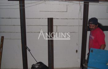steel support beams in a basement of a bulding and with cracks between the bricks filled, one anglin employee is in the side of the photo