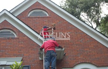 two anglins employees working on a roof of a house