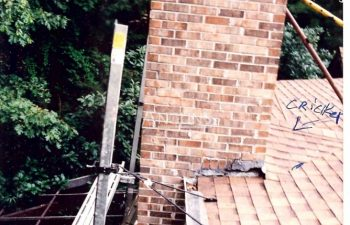 a house with a chimney that is leaning - photo during a repair and the chimney is supported by metal rods