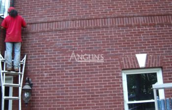 an anglin employee filling cracks in a wall