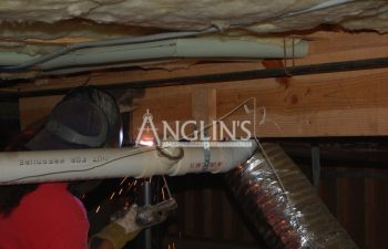 anglin's worker welding a pier supporting a sinking floor