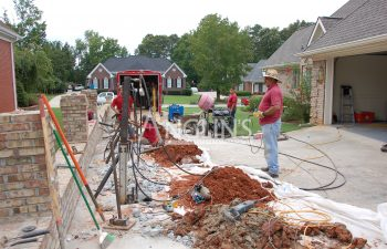 three anglin employess working on leveling a driveway, there are hydraulic piers in the ground raising the driveway