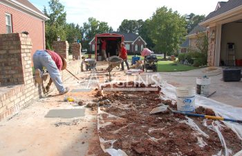 three anglin employees cleaning the driveway after it was leveled and the holes for the hydraulic piers were filled
