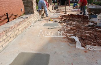 two anglin employees cleaning the driveway after it was leveled and the holes for the hydraulic piers were filled