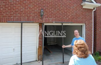 anglin's employee explaining the repair process to the client in front of damaged garage door