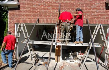 three anglin employees working on two garage doors