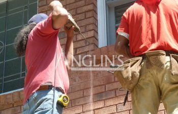 two anglin employees working on a house, one is drilling in a wall