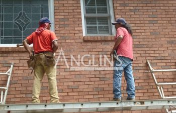 two anglin employees working on a house