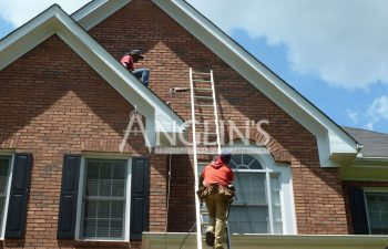 two anglin workers doing their job on a roof of a house