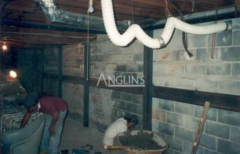 steel support beams in a basement of a bulding and with cracks between the bricks filled, there are two anglin employees working next to it