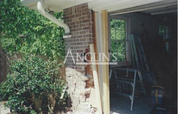 damaged garage brick wall and the garage door