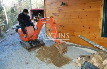 an anglin employee digging a hole with a mini excavator