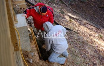 anglin's employees excavating deck foundations