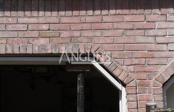 crack in a brick wall over a garage door