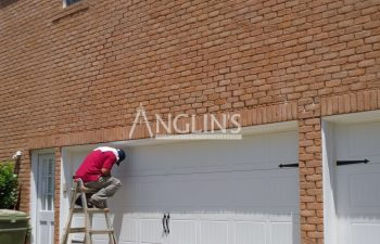 anglin's employee sitting on the top of the ladder while fixing the garage door