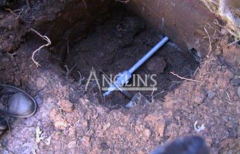 excavation with an anchor installed in a brick wall foundation