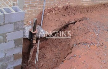 excavation at exterior brick house wall
