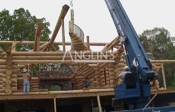 photo of the cabin being build with a crane raising a log