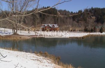 photo of the cabin from a distance with a lake in the foreground