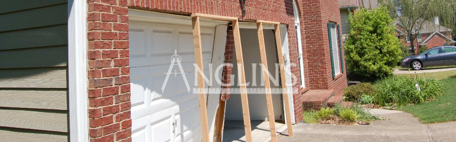 two wooden support frames in front of garage doors which need repair